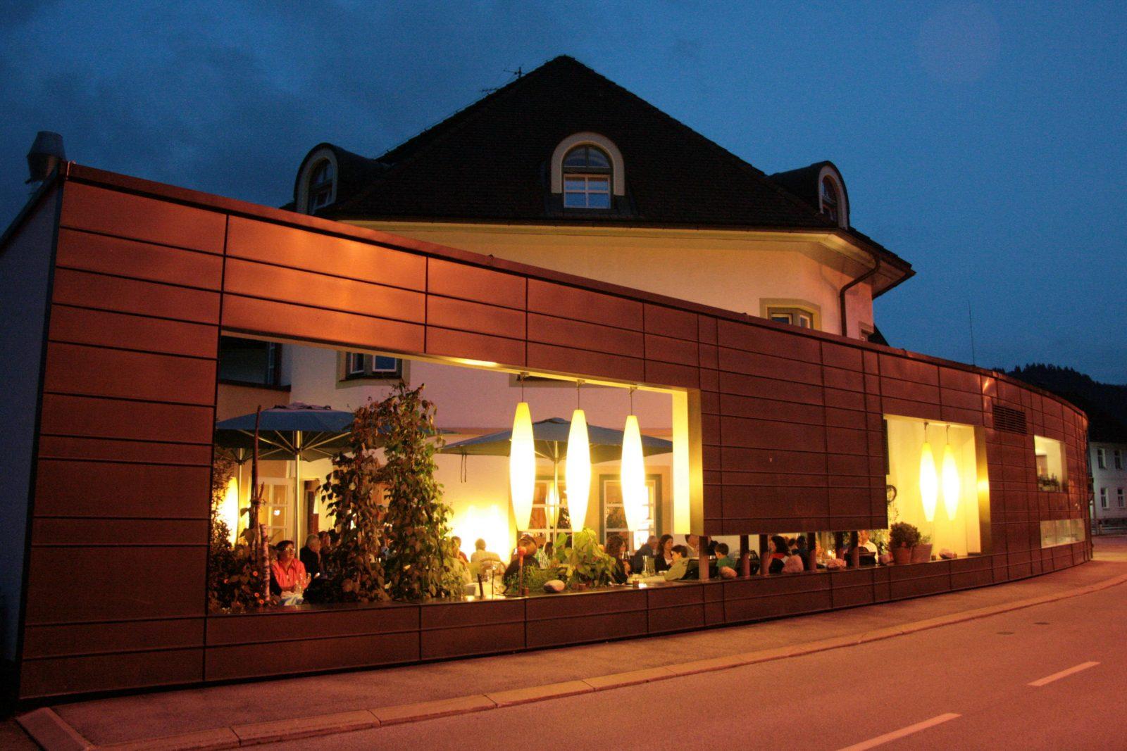 Garten Terrasse mit Gästen bei Nacht und Beleuchtet mit Zigarrenleuchten