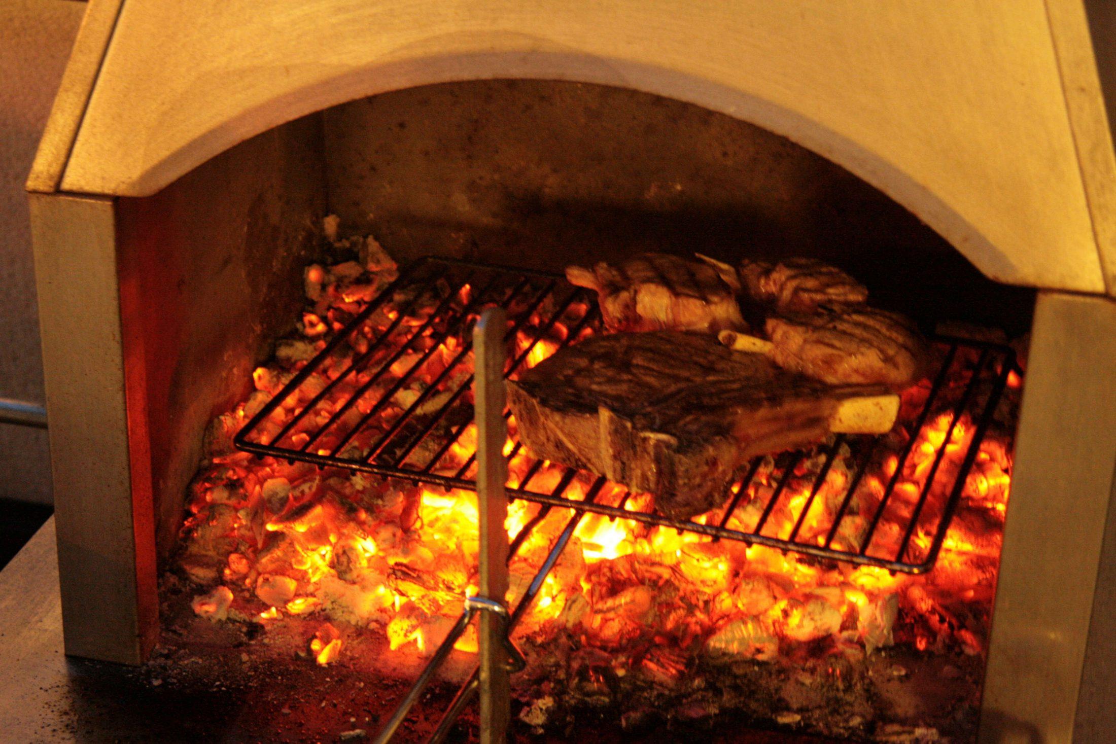Steak mit Knochen auf Rost am Griller beim Grillabend