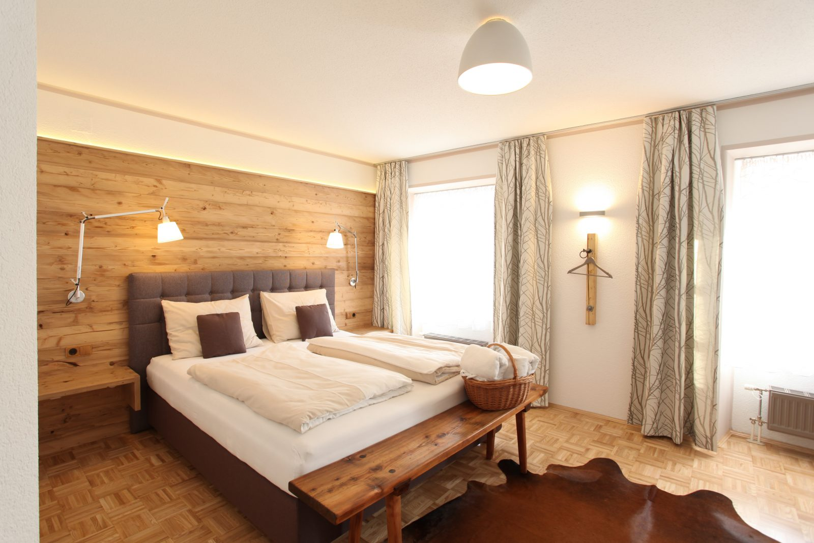 Hotelzimmer mit Fichtenholzvertäfelung und Boxspringbett