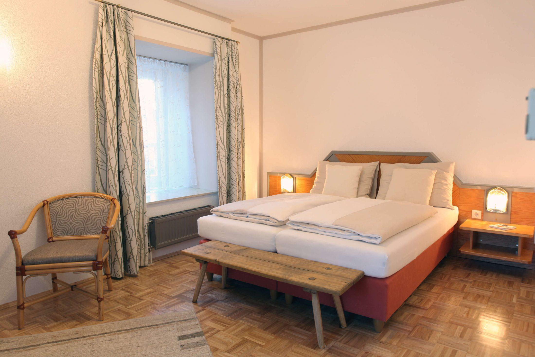 Hotelzimmer mit Doppelbett, rustikale Bank