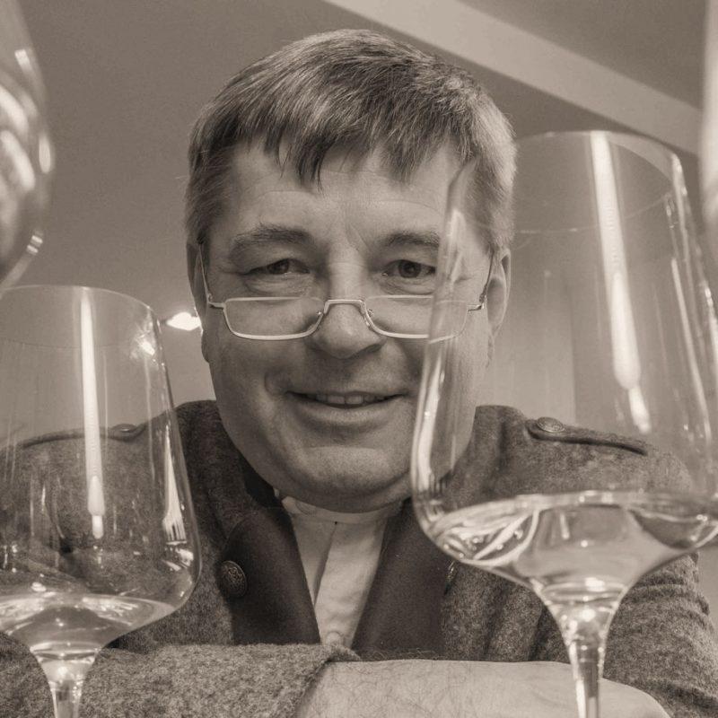 Krainer Hermann lächelt in die Kamera mit einem Glas Wein