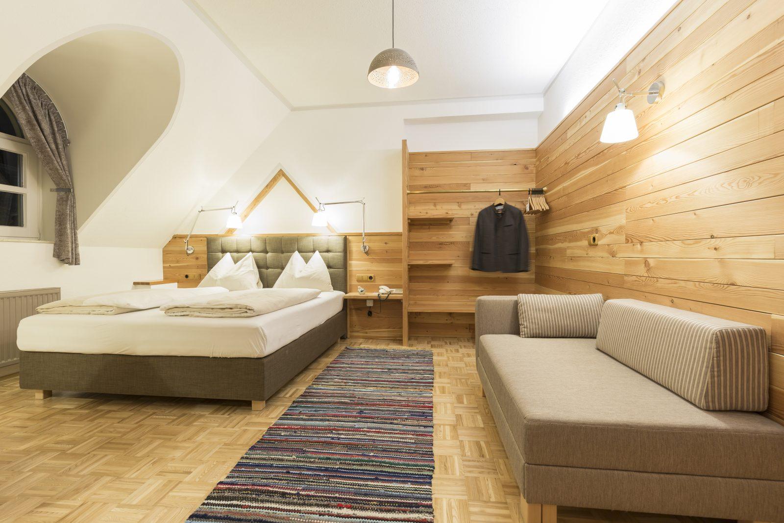 Hotelzimmer mit Lärchenholzvertäfelun und Boxspringbett